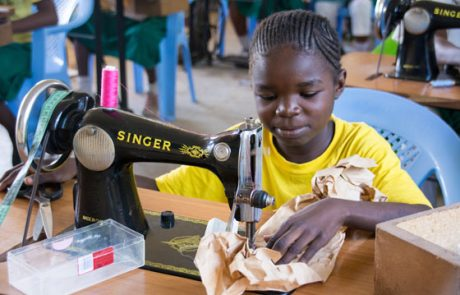 Mädchen arbeitet an Singer-Nähmaschine